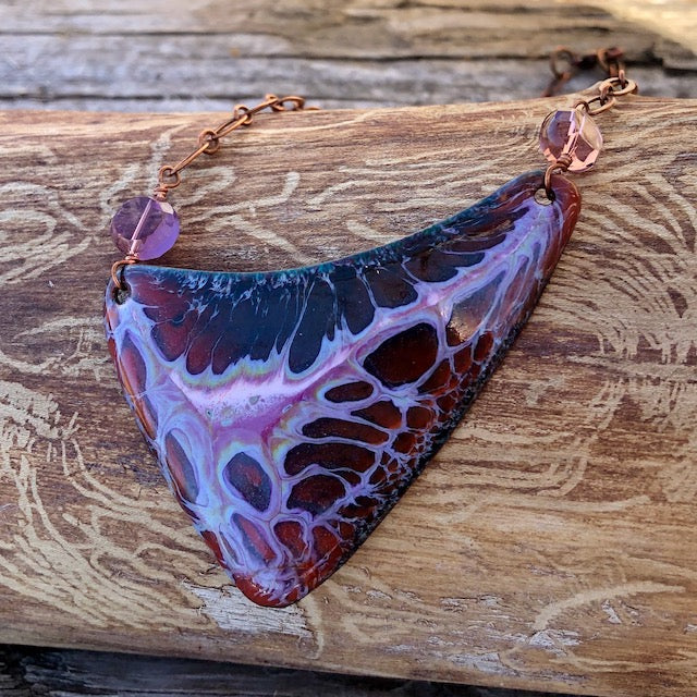 Triangular copper enamel pendant in deep maroon and pink on a copper chain necklace.