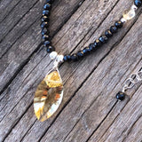 Closeup of marquise cut citrine pendant necklace with black spinel and sterling