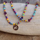 Multicolored stretch necklace or triple wrap bracelet with bronze dog and bone charm and purple Swarovski crystals