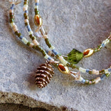 Closeup stretch necklace or triple wrap bracelet with bronze pine cone charm, Swarovski crystals, and green, pink and blue seed beads
