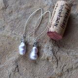 Elegant baroque pearl and Swarovski crystal earrings on long oval ear wires. Cork for size reference.