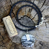 "Black silk agate stone pendant necklace with silver ""hope"" charm on twisted rubber cord with cork for size reference"