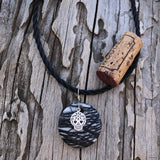 Black and gray striped agate stone pendant necklace with silver sugar skull charm on twisted rubber cord. Cork for size reference.