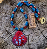 Dappled red and blue enamel pendant necklace with blue shell and red coral beads. Cork for size reference.