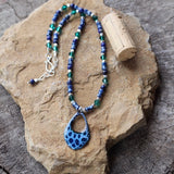 Blue enamel pendant necklace with green Swarovski crystals, blue lapis beads and sterling silver accents. Cork for size reference.