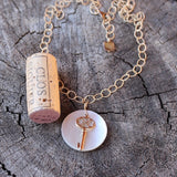 Bronze key with pearly shell pendant on 14k gold filled chain. Cork for size reference.