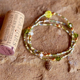 Stretch necklace or triple wrap bracelet with bronze pine cone charm and pink, green, and blue seed beads. Cork for size reference.