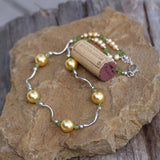 Necklace with golden pearls, peridot and wavy sterling tube beads and cork for size reference