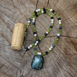 Green and blue dichroic glass pendant necklace with peridot, freshwater pearls and blue goldstone.  Cork for size reference