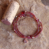 Stretch necklace or triple wrap bracelet with sterling equality charm in red bead mix.  Cork for size reference.