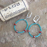 Flexible hoop earrings with turquoise seed beads and orange crystals with cork for size reference
