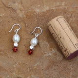 Earrings with white freshwater pearls, sterling cube beads and burnt orange Swarovski crystals and cork for size reference