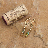 Green and gold crystal earrings with gold-filled ear wires and cork for size reference