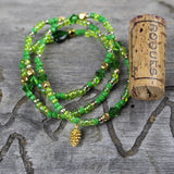 Green beaded stretch necklace or triple wrap bracelet with gold vermeil pine cone charm. Cork for size reference.