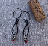 Bohemian style leather loop earrings with intricate Thai silver beads and Swarovski crystals. Cork for size reference.