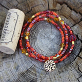 Orange beaded stretch necklace or triple wrap bracelet with bronze tree of life charm.  Cork for size reference