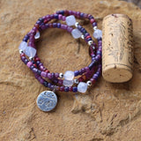Stretch necklace or triple wrap bracelet with camping charm and purple glass beads with blue lace agate cube beads. Cork for size reference.