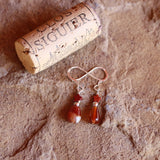 Red agate drop with red jasper star earrings on sterling silver ear wires. Cork for size reference.