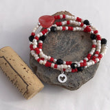 Stretch necklace or bracelet with red, white and black beads with tiny silver heart cutout charm and cork for size