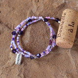 Purple beaded stretch necklace or triple wrap bracelet with sterling believe charm and deep violet Swarovski crystals. Cork for size reference.