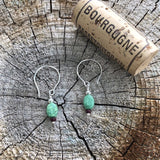 Simple sterling silver earrings with turquoise oval beads. Cork for size reference