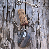 "Agate stone pendant necklace with sterling silver ""explore"" charm on sterling ball chain. Cork for size reference."