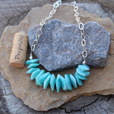 Bib style statement necklace with amazonite nuggets on sterling hammered chain. Cork for size reference.