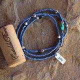 Stretch necklace or triple wrap bracelet with blue seed beads and a sterling silver joy charm. Cork for size reference.