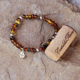Golden amber nuggets stretch bracelet with sterling silver accent beads and a sterling compass charm. Cork shown for size reference.