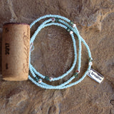 Stretch necklace or triple wrap bracelet with aqua seed beads and a sterling silver breathe charm. Cork for size reference.