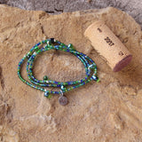 Stretch necklace or triple wrap bracelet with a mix of green and blue seed beads and a sterling tiny heart charm. Cork shown for size reference.