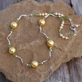 Necklace with golden pearls, peridot and sterling silver wavy tube beads
