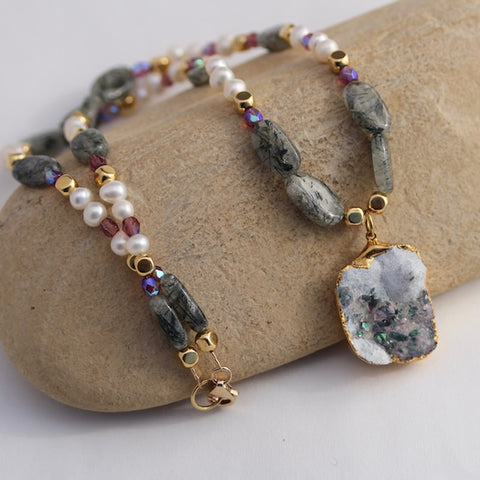 Gold-rimmed druzy pendant necklace with green rutile, freshwater pearls, crystals and brass