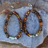Flexible hoop earrings with amber beads and a single turquoise bead highlighted with satin finish sterling beads. Sterling silver lever back ear wires.