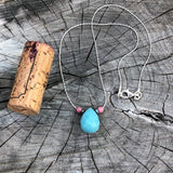 Faceted amazonite drop pendant necklace on sterling chain with hematite and rhodochrosite accent beads. Cork for size reference.