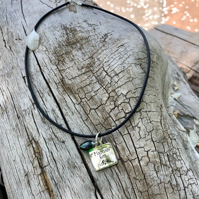 Stainless steel pendant with Mountain Girl etched on it on a rubber cord necklace with a green glass heart bead.