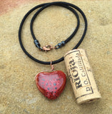 Red ceramic heart necklace on black cotton cord with cork for size reference