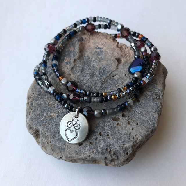 Bike love charm stretch necklace or triple wrap bracelet with multicolored seed beads and garnet red Swarovski crystals.