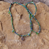 Stretch necklace or triple wrap bracelet with sterling tiny heart charm and a mix of blue and green seed beads. Green glass drop beads are interspersed along the strand.