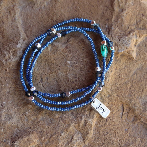 Stretch necklace or triple wrap bracelet with blue seed beads and a sterling joy charm