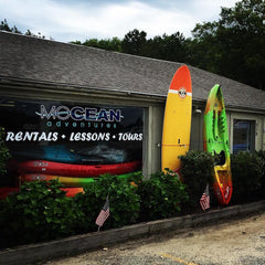 kayaks and paddle boards for rent outside mocean cape cod at the mashpee rotary