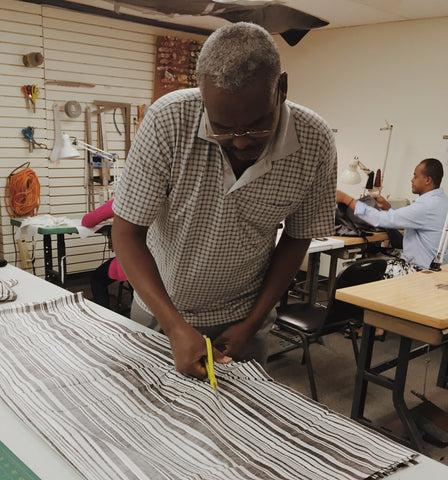 Man cutting fabric at New Vestures in Lowell Ma