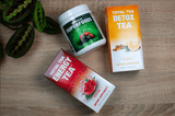 Total Tea & Chiroflex Superfood Green Supplement with Berries and Curcumin powder shown with Detox Tea and Energy Tea products on wooden surface.