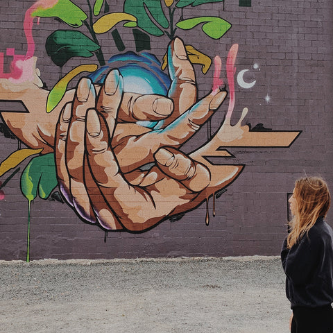 girl standing in front of an outdoor graffiti piece of hands holding the world