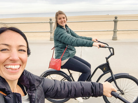 two girls bike riding on beach