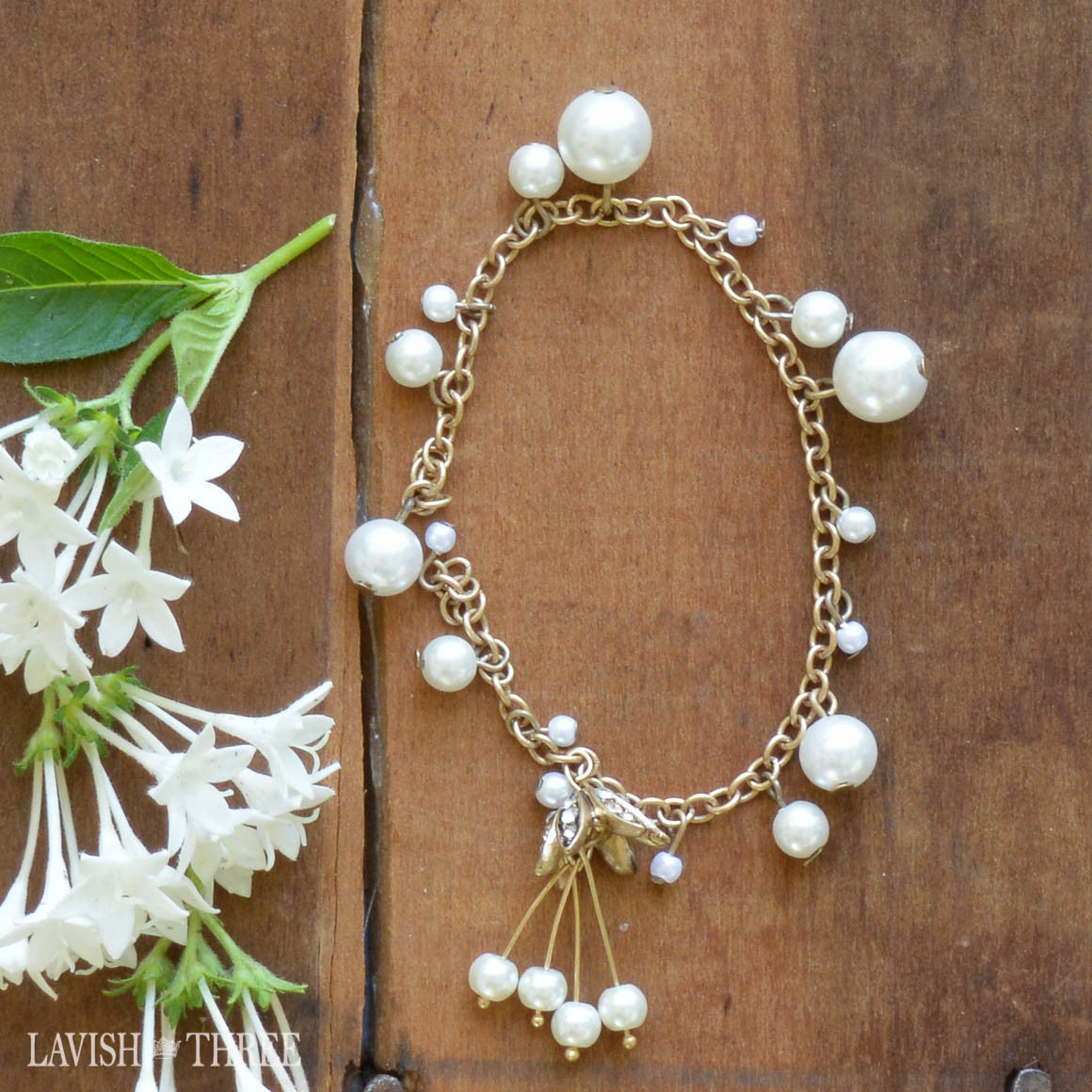 Gold and pearl bracelet with flower charm