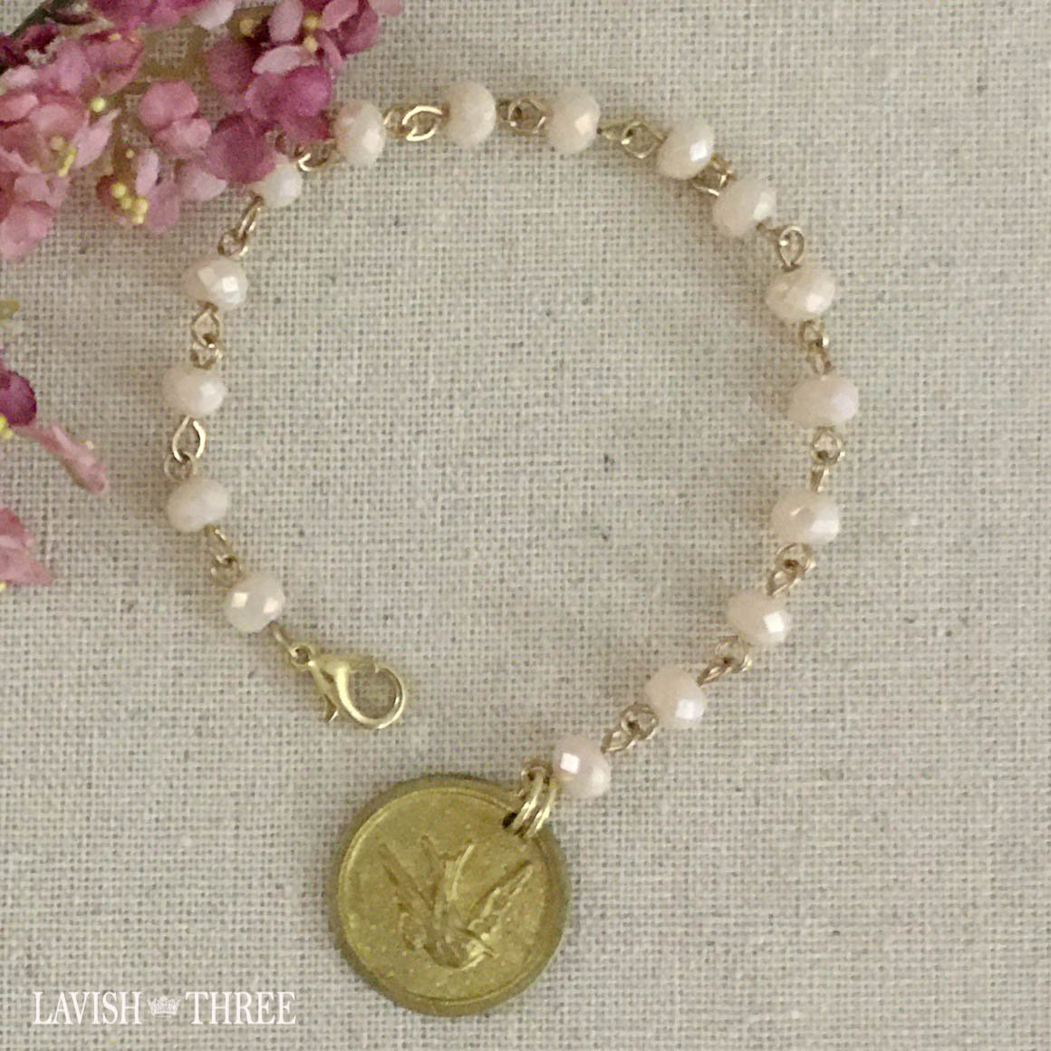 Gold bird charm on pale peach flesh color beaded bracelet lavish three 3