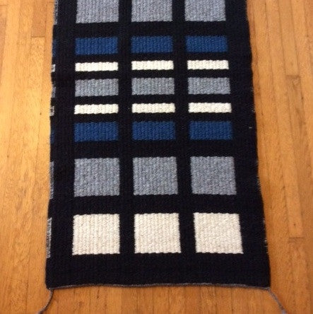 This area rug by Linda Morton-Keithley has blue, gray, and natural wool colored blocks on a black background.