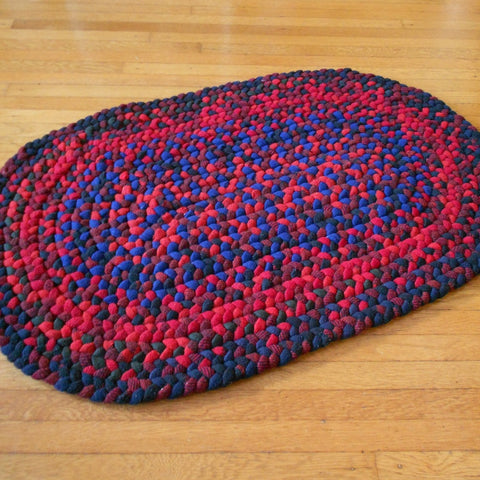 This thick oval hand braided rug was made with Pendleton wool fabrics in red, deep blue, black, and maroon.