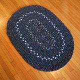 This deep gray hand braided wool rug has has accents of sky blue. It was made from Pendleton wool fabrics.